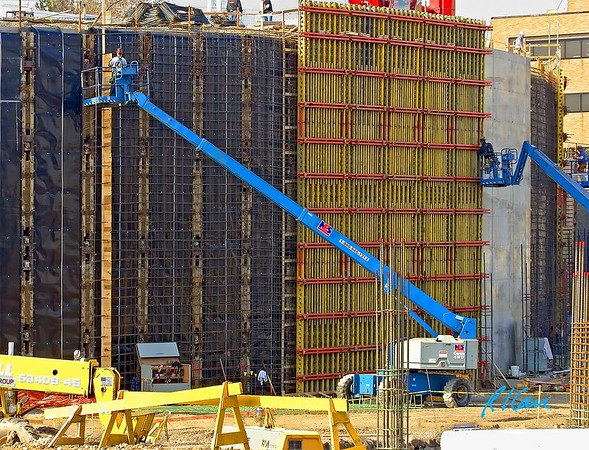 Concrete construction: Carpenter, supported by Genie telescoping personnel lift, pulls fits pieces of cut  lumber for bulkhead in formwork for concrete placement for retaining wall. Bulkhead forms a short term construction joint in the concrete, until the next section of concrete is placed to the left. Cardiovascular Center, University of Michigan Hospital, Ann Arbor, 2004.