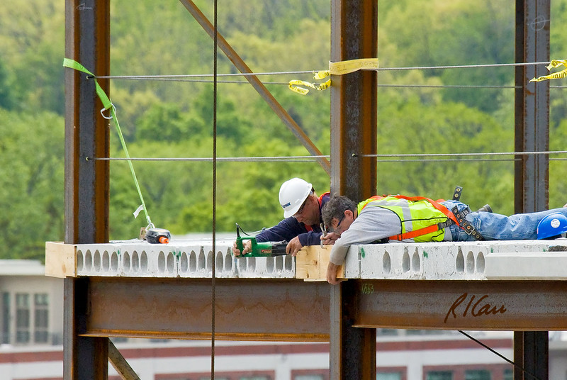 Two workers lie down to place small plywood form on outside of exterior column to place concrete in gap between edge portions of precast hollow core floor slabs. Far worker is drilling through form into concrete to attach form to the concrete. The metal clasp at top is tied back to ensure the form does not fall if workers release it by mistake. A similar form is in place on the building corner to left of photo. Ashley Terrace, Ann Arbor, Michigan April, 2007.