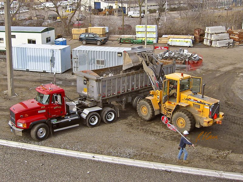 Pavement construction demolition: Volvo L90D wheel front-end loader dumps debris into rear dump truck. Broadway Bridge, Ann Arbor, 2003