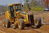 Earthmoving, road construction: John Deere 670CH motor grader rough grades soil base in preparation for soil compacting roller. South approach from Huron River Drive onto Dixboro Bridge over Huron River. Ann Arbor, Michigan 2005.