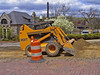 Pavement construction: Case 95XT skid steer tractor with front end loader attachment moves forward, with front wheels off ground, and grades/levels pavement base soil while filling shovel with soil. Depot Street, Ann Arbor, 2004