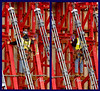 Construction safety, fall protection: Worker supported by pipe on rear of gang form moves from one bay to the bay on its right, maintaining his fall protection by moving his two safety lanyard-hooks one at a time from his left side to his right. (He has moved from left of the blue-circled point to right of it.) Photo provides close-up view of galvanized steel (gray) turnbuckle columns that slope down from left to right, that can be rotated to push/pull form face against/away from the concrete. Michigan 2006