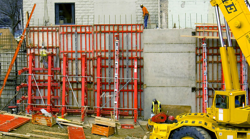 Worker on forms at left is knocking form bolts loose to separate gang forms from concrete basement wall they cast. A worker walks along top of concrete basement wall more than 20 feet above the ground, among reinforcing bar tripping hazards, without all protection. He carries two safety lanyards and hooks, attached to full body harness and hooked temporarily at his right chest. Right foreground is Grove telescoping boom hydraulic crane. Michigan 2006.