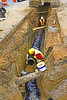 Trench construction, safety: Caterpillar 3128 crawler mounted backhoe moves large pipe section/spool into trench to construct underground pipe. Workers standing in 8 ft deep trench have no support against sidewall collapse. Near worker is applying pipe joint lubrication in preparation for inserting pipe spool/segment into previously placed pipe. Worker safety and the law require: (1) Trenches 5 feet (1.5 meters) deep or greater must be supported or sloped back unless the excavation is made entirely in stable rock, and this soil is not stable rock. (2) Workers must have easy, close exit from trenches, which pipes crossing this trench prevent. Michigan 2006