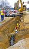 Trench construction, safety: Caterpillar 3128 crawler mounted backhoe moves large pipe section/spool into trench to construct underground pipe. Workers standing in 8 ft deep trench have no support against sidewall collapse. Worker safety and the law require: (1) Trenches 5 feet (1.5 meters) deep or greater must be supported or sloped back unless the excavation is made entirely in stable rock, and this soil is not stable rock. (2) Workers must have easy, close exit from trenches, which pipes crossing this trench prevent. Michigan 2006