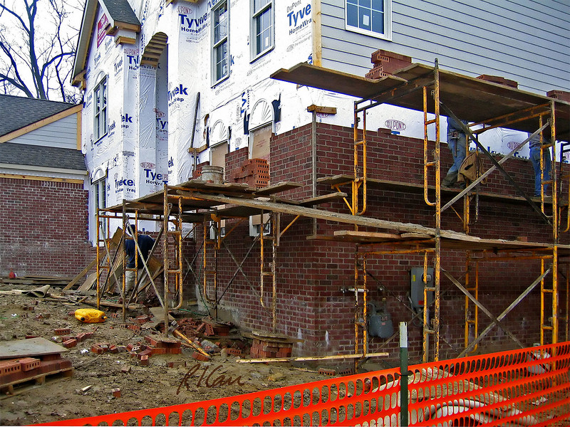 """Masonry construction, construction safety: Manufactured tubular scaffold posts supported at base by unstable brick cribbing. Preferred methods would include screw-jacks at scaffold bases extended to stable mud sill or other stable footing. 2"""" x 10"""" wood planks form working platform for masons to stand on and a higher material platform on which masonry units (brick here) and mortar are placed. The outside of the material level should have guardrails to protect laborers placing and stacking brick and working with mortar. The ramp between the side and front sections of scaffold should also have guardrails and also cleats for good footing, especially in the wet weather in which masons are working. Ann Arbor, Michigan, 2004<br />     OSHA 1926-L requires: Supported scaffold poles, legs, posts, frames, and uprights shall bear on base plates and mud sills or other adequate firm foundation. Footings shall be level, sound, rigid, and capable of supporting the loaded scaffold without settling or displacement. Unstable objects shall not be used to support scaffolds or platform units."""