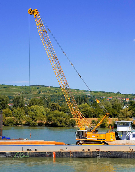 Marine/river construction: Construction barge carries Liebherr crawler mounted lattice boom, cable operated crane and ABI Mobilram drill and vibratory/ impact/ pressing pile driving rig. Crane lifts steel sheet piles that lay in front of it and feeds them to the pile driving rig. Danube River in Hungary west of Budapest, August 2006.