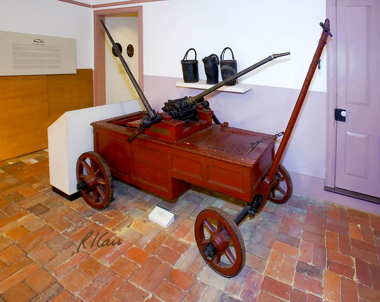 "The Original George Washington Engine. Hand pumper owned by the Friendship Fire Company and used from 1775 until 1849, when it was replaced by the Rodgers pumper. It is purported that George Washington, a resident of Alexandria, Virginia, was a member of the Friendship Fire Company and that he purchased the pumper for the Company for 18 pounds 10 shillings after observing a similar pumper in Philadelphia, Pennsylvania in 1774 while at the Continental Congress. Friendship Firehouse Museum, Alexandria, Virginia, November 2006.<br />      ""One of the earliest types of fire engines used in America, this rotary engine was probably built about 1770 in England, by Newsham and Ragg. Sometimes referred to as a 'coffee grinder' engine, it was cranked by two pairs of men. As they cranked, blades rotating around a central shaft forced water from the central chamber through a nozzle onto the fire. Although water still had to be emptied into the chamber by bucket brigades, when it was pumped through the engine, it propelled a steady stream of water, a great improvement over throwing individual buckets of water at the flames."" (From Museum notes)"