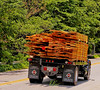 International flat bed truck loaded with lumber stacked high and held in place with woven plastic straps. Groton, Massachusetts, 2007. By Rob Carr.